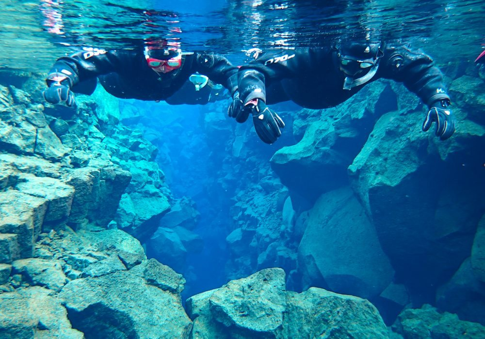 Two persons snorkeling in Silfra Fissure