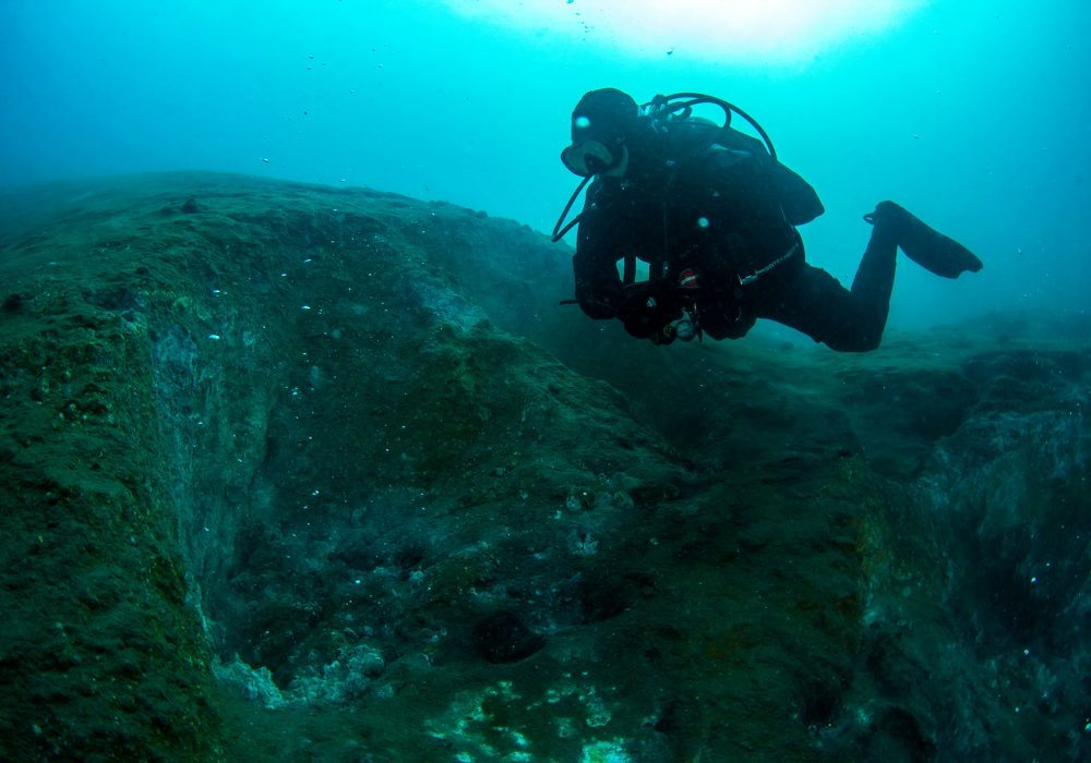 Diver exploring geothermeral formations in Kleifarvatn, on a scuba diving tour in Lake Kleifarvatn, Iceland