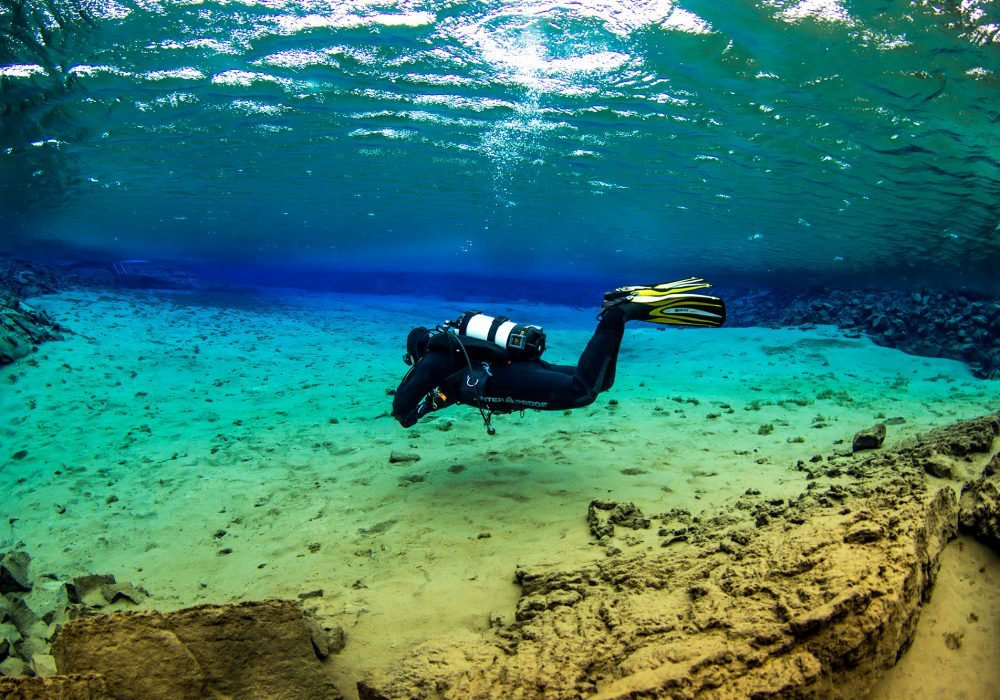 Diving tour in Iceland, scuba diver exploring the Silfra Fissure