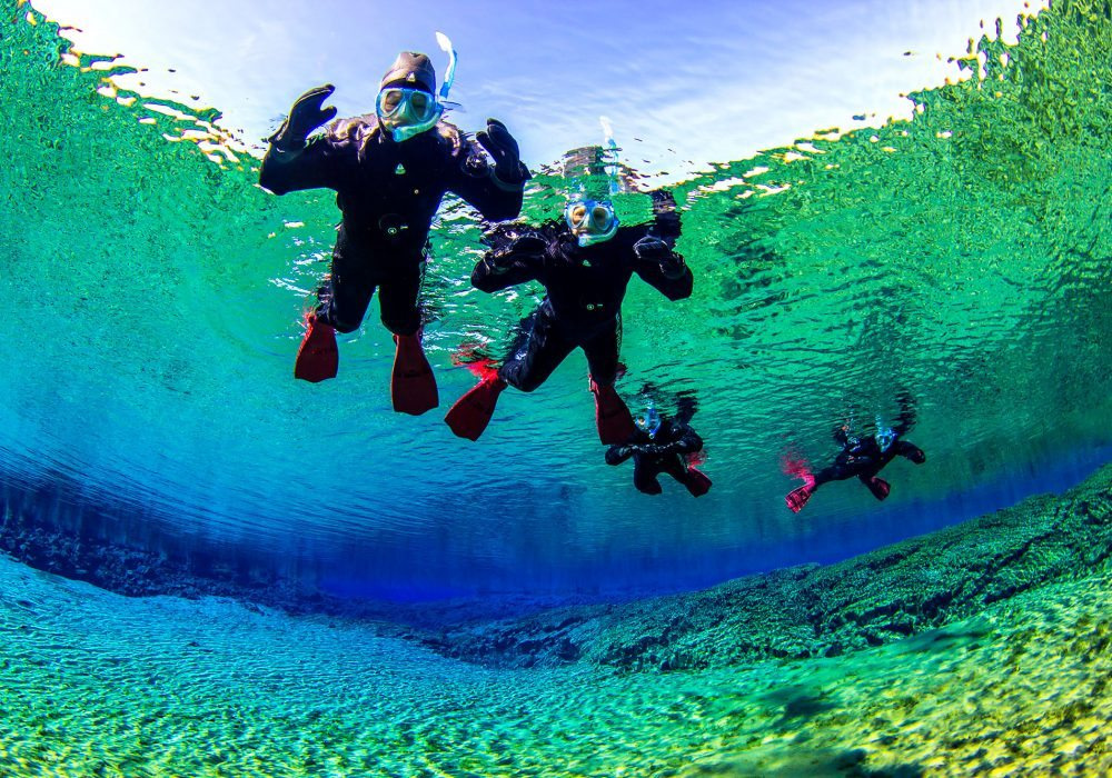 Four snorkelers in the Silfra Lagoon during a snorkeling tour in Iceland