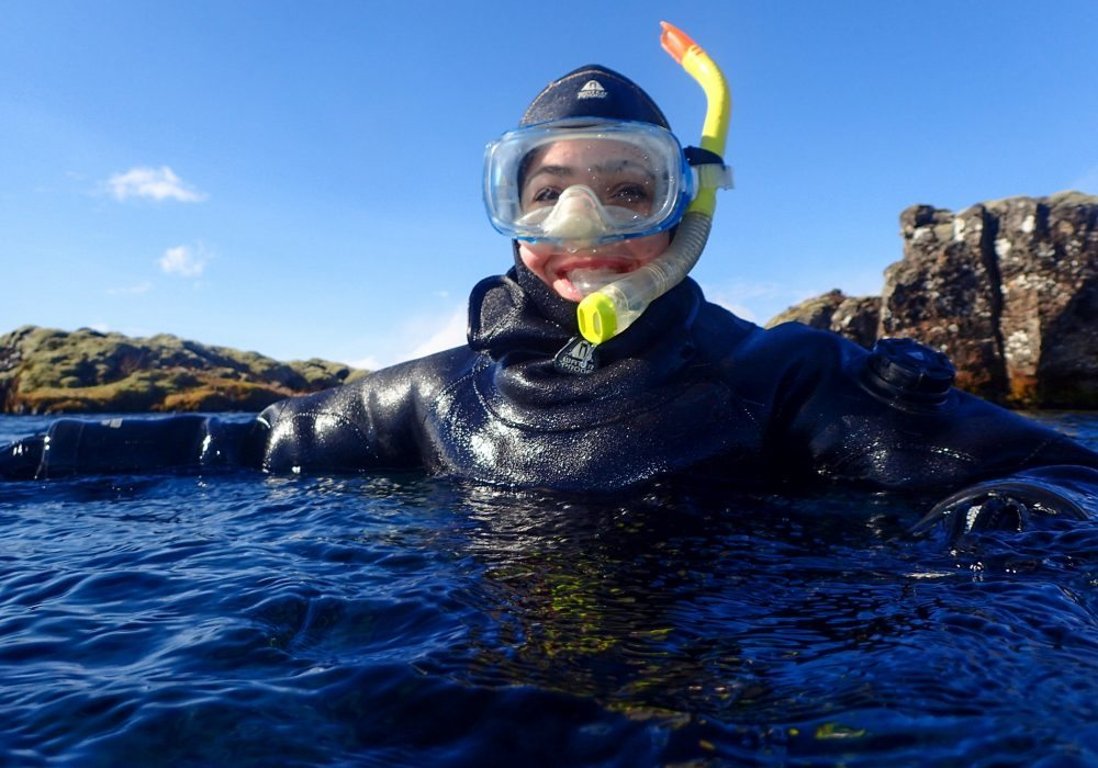 Girl is snorkeling in Silfra fissure
